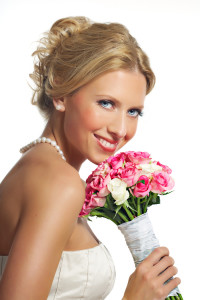 Smiling tanned bride with pink roses over white.